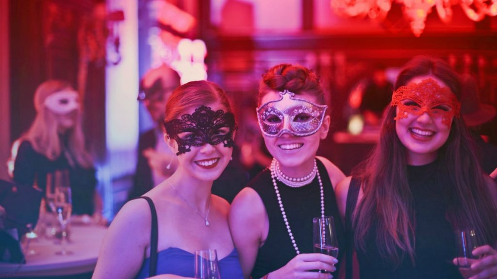 girls wearing mask holding a glass of wine