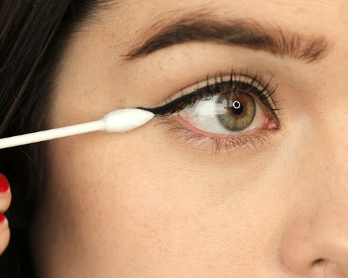 eyeliner using a cotton  bud
