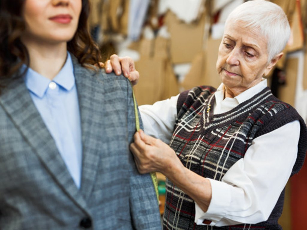 old lady measuring woman's sleeve length